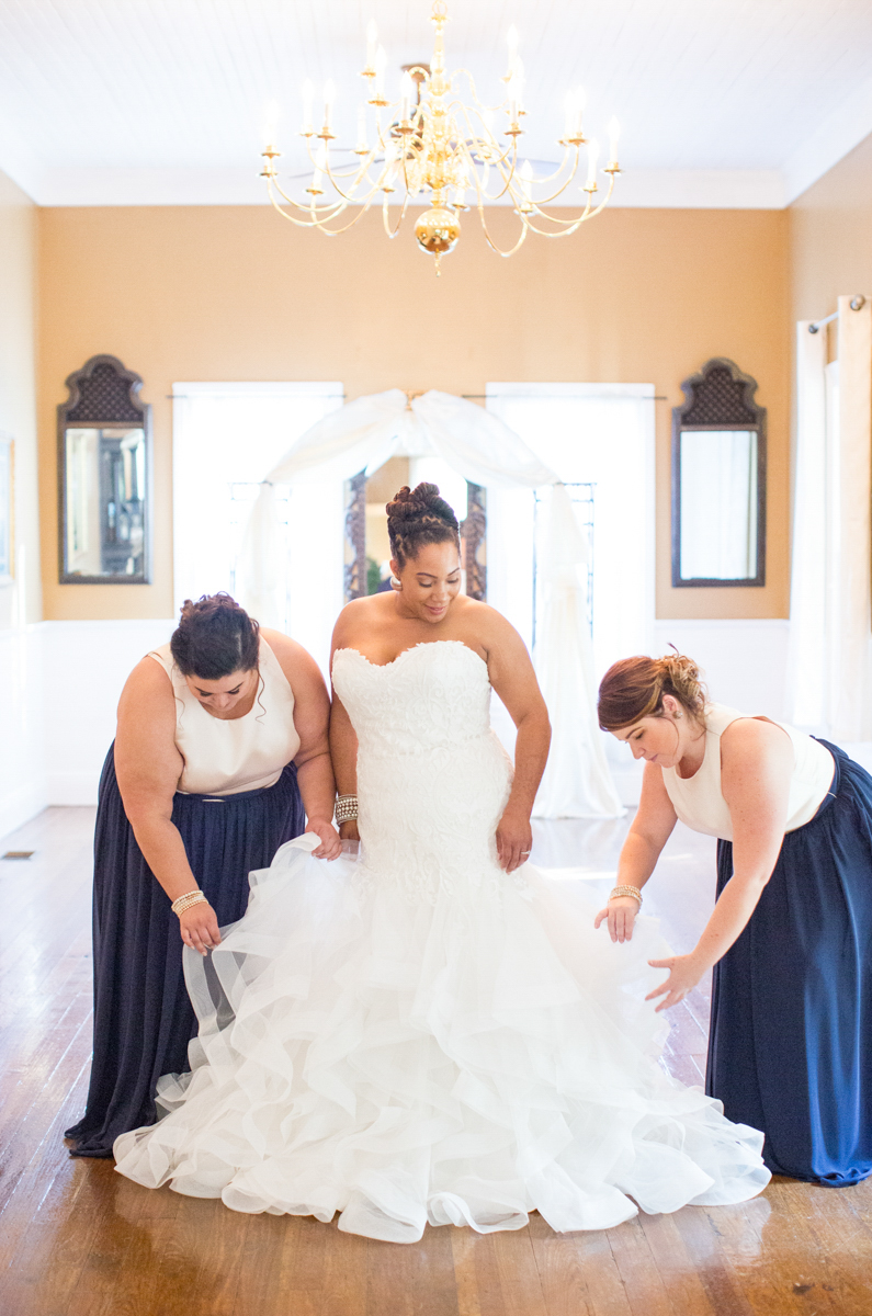 Bride and bridesmaids fixing gown