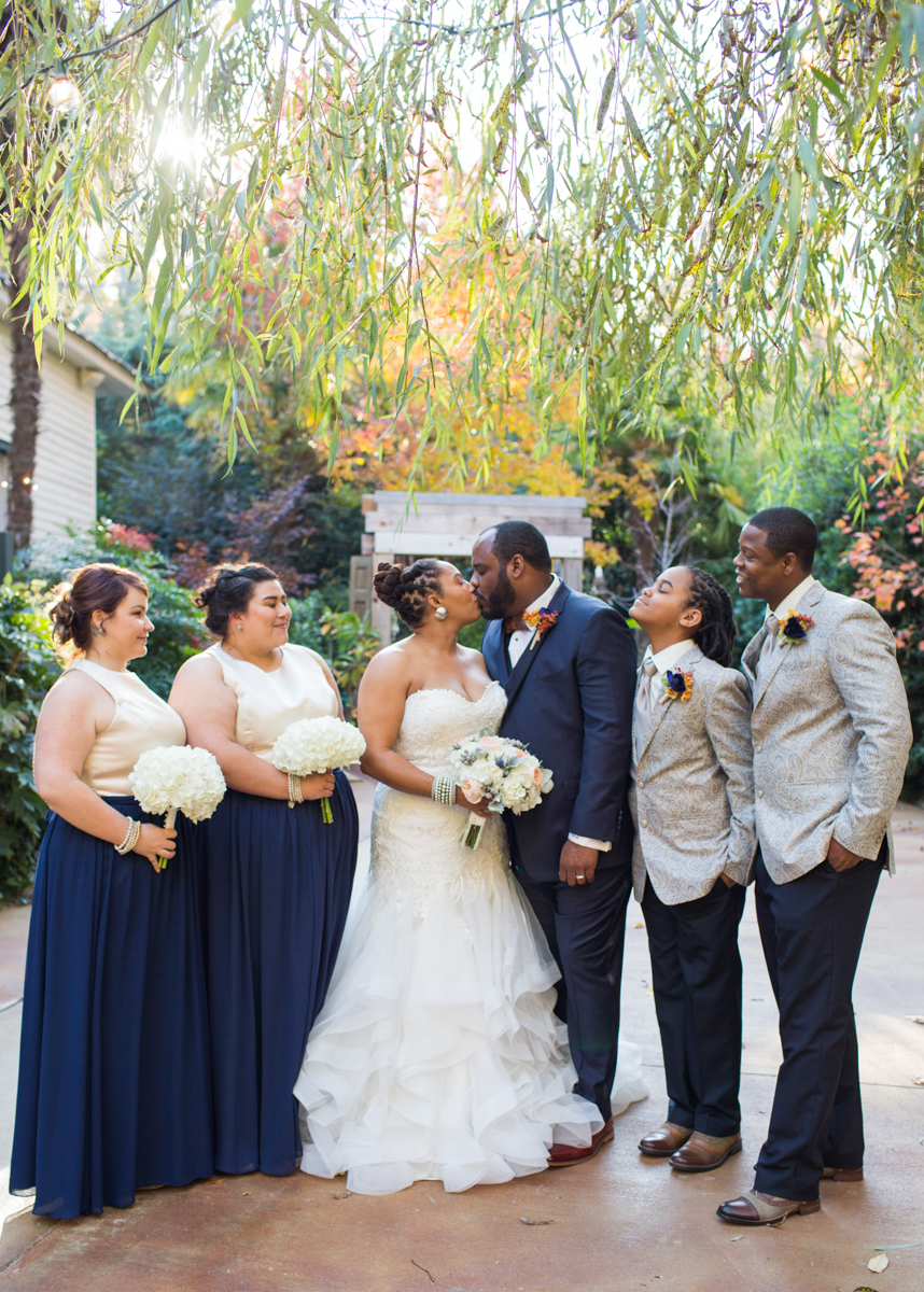 Entire wedding party, with couple kissing