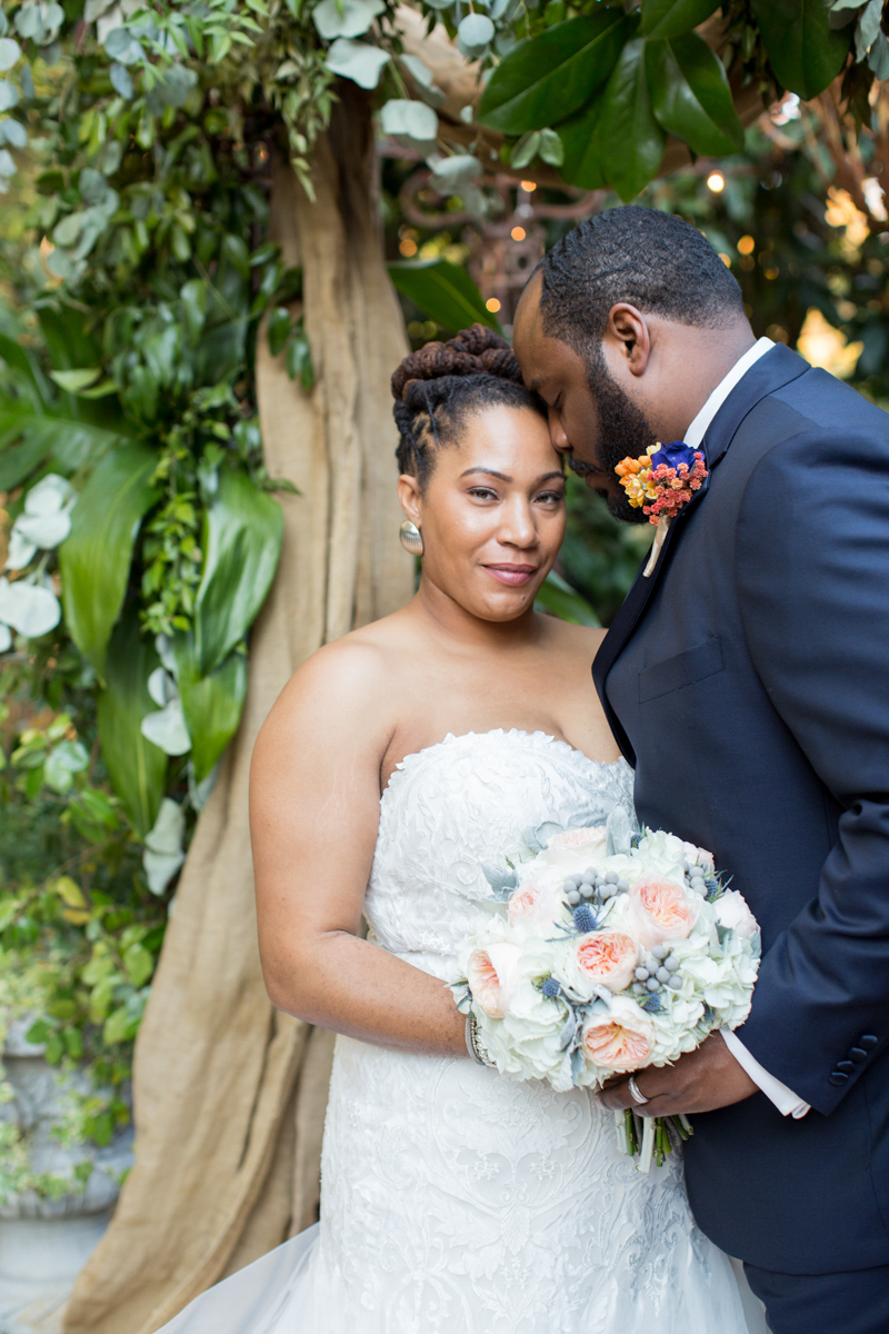 Black bride and groom posing at their wedding arch