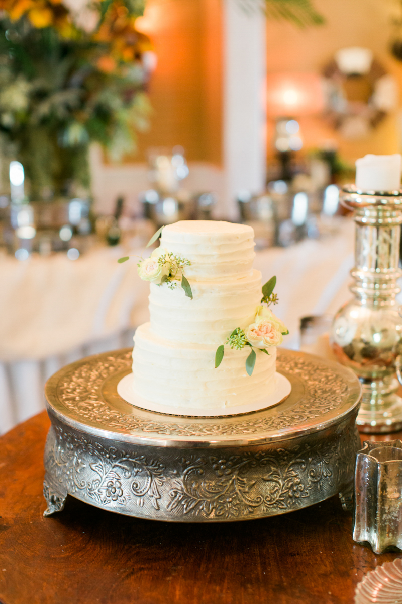two tiered white wedding cake with roses on
