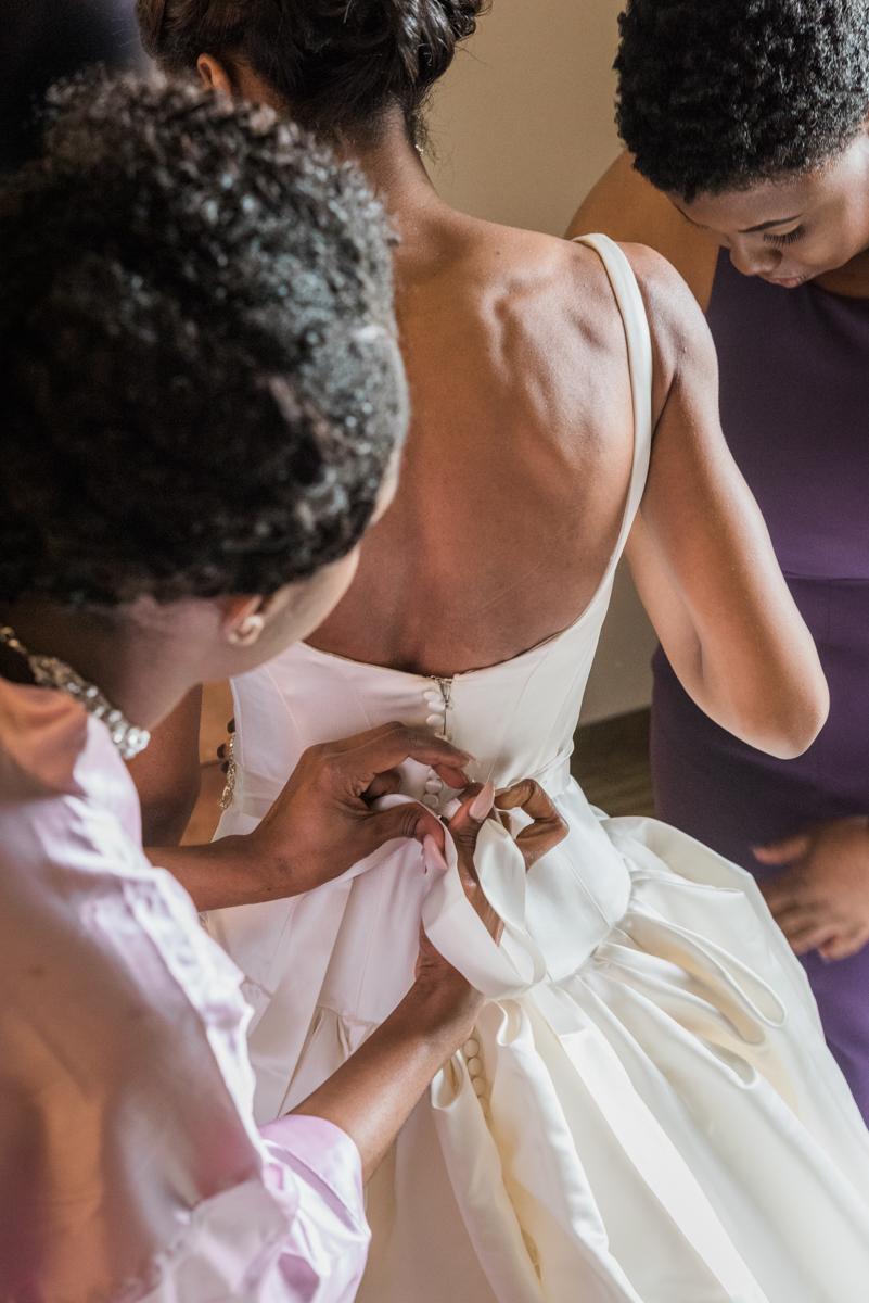 mother buttoning bride's gown