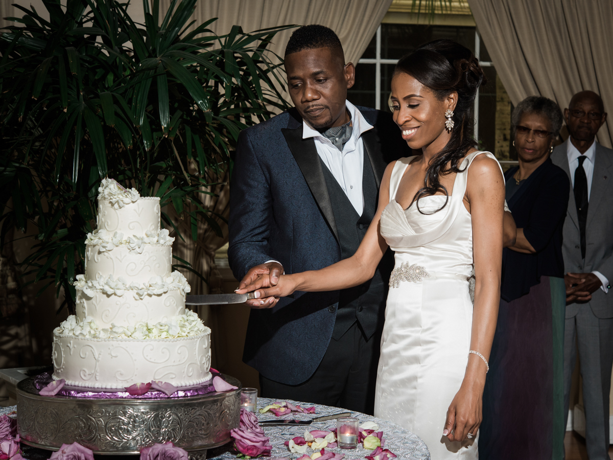 bride and groom cutting their classic white wedding cake
