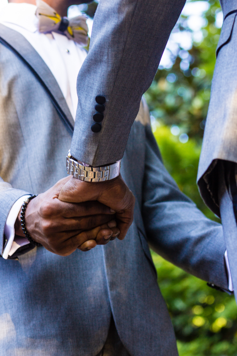 grooms holding hands at their wedding ceremony