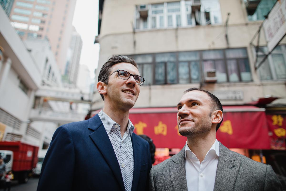 a couple at their engagement session, looking up at hong kong