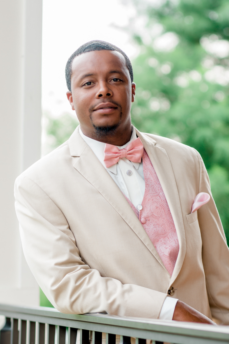 Classic groom portrait with groom wearing cream suit and pink bowtie