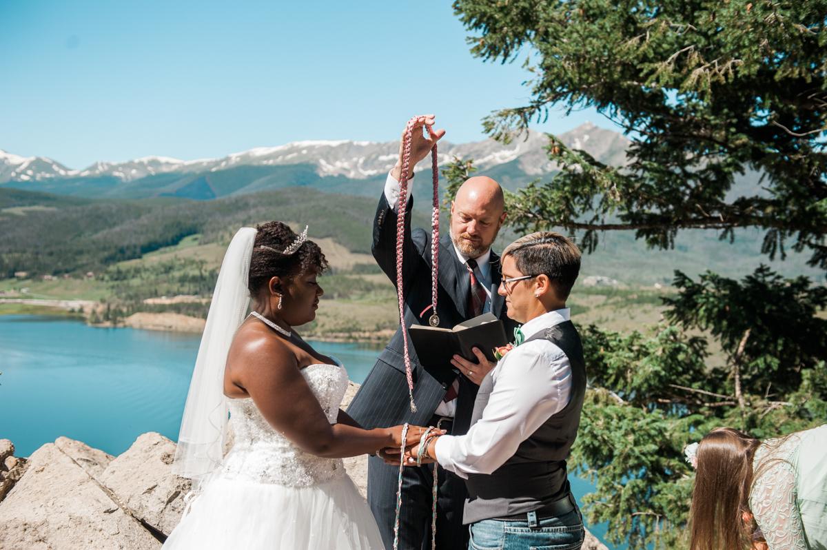 mountain elopement tying hands