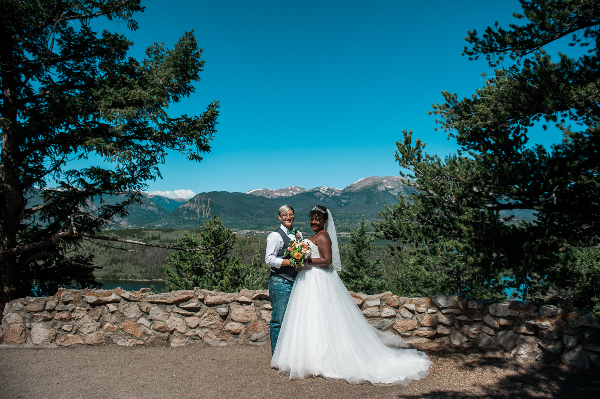 mountain elopement brides pose in front of skyline