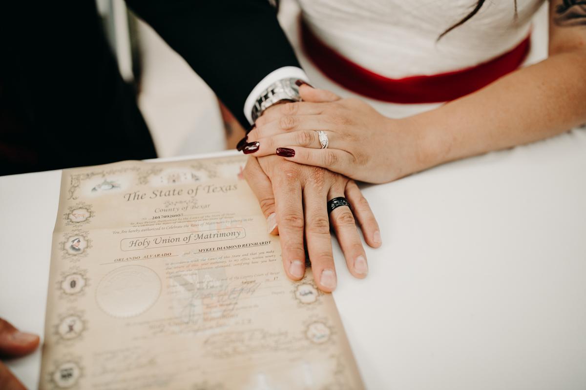 San antonio garden wedding hands with wedding rings and invitations
