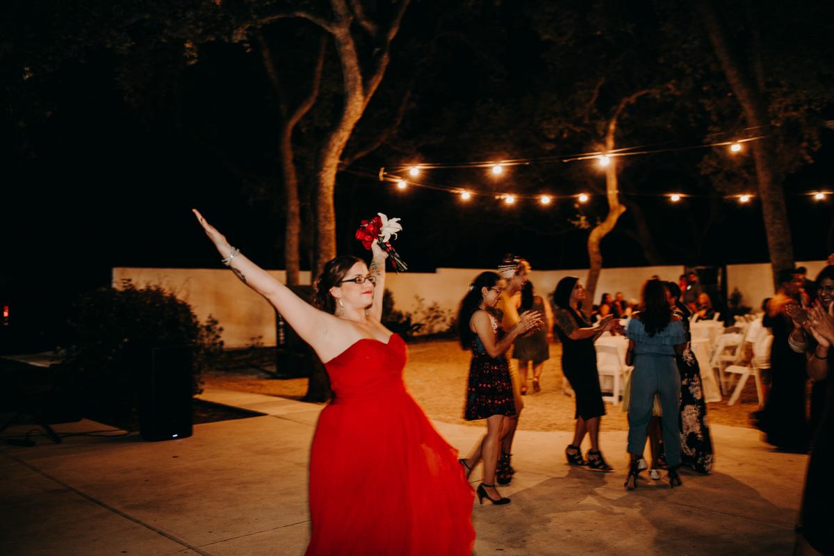 San antonio garden wedding bridesmaid with bouquet raised victoriously