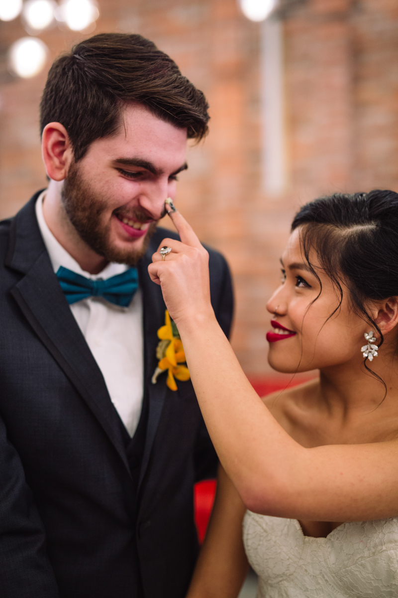 williamsburg hotel wedding shoot bride dabbing groom's nose with frosting