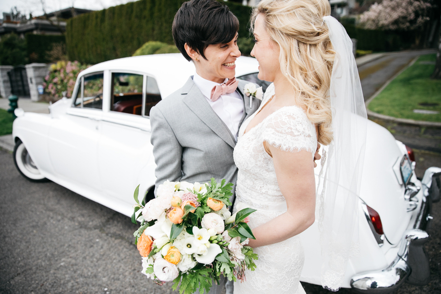 ARIN AND KATIE DOWNTOWN SEATTLE WEDDING COUPLE SMILING WITH CAR IN BACKGROUND