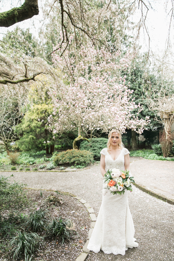 ARIN AND KATIE DOWNTOWN SEATTLE WEDDING KATIE WITH BOUQUET UNDER BLOSSOMING TREE