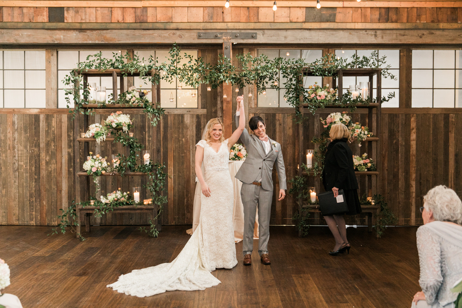 ARIN AND KATIE DOWNTOWN SEATTLE WEDDING couple's clasped hands raised as ceremony concludes