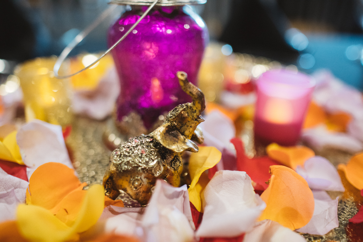 DENVER SAME-SEX INDIAN WEDDING TABLE WITH SMALL ELEPHANT STATUE AND FLOWER PETALS