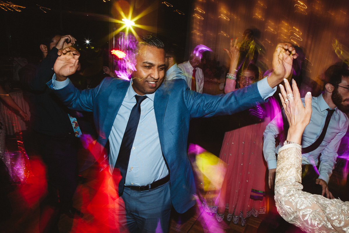 denver same-sex indian wedding guests dancing with blurry camera affect