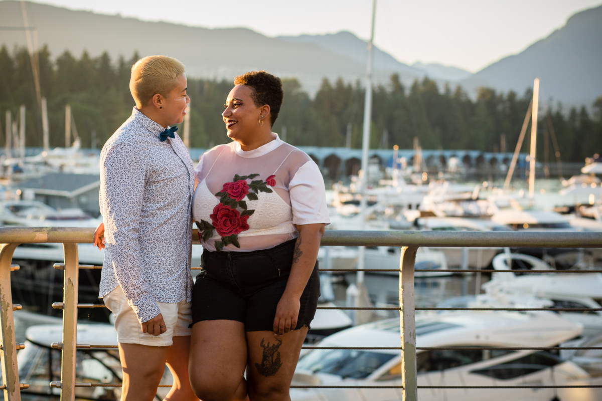 """vancouver """"just because"""" photo shoot couple smiling on bridge in front of boat-filled docks"""