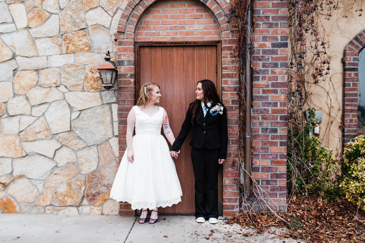 Rustic italian wedding couple holding hands in front of door