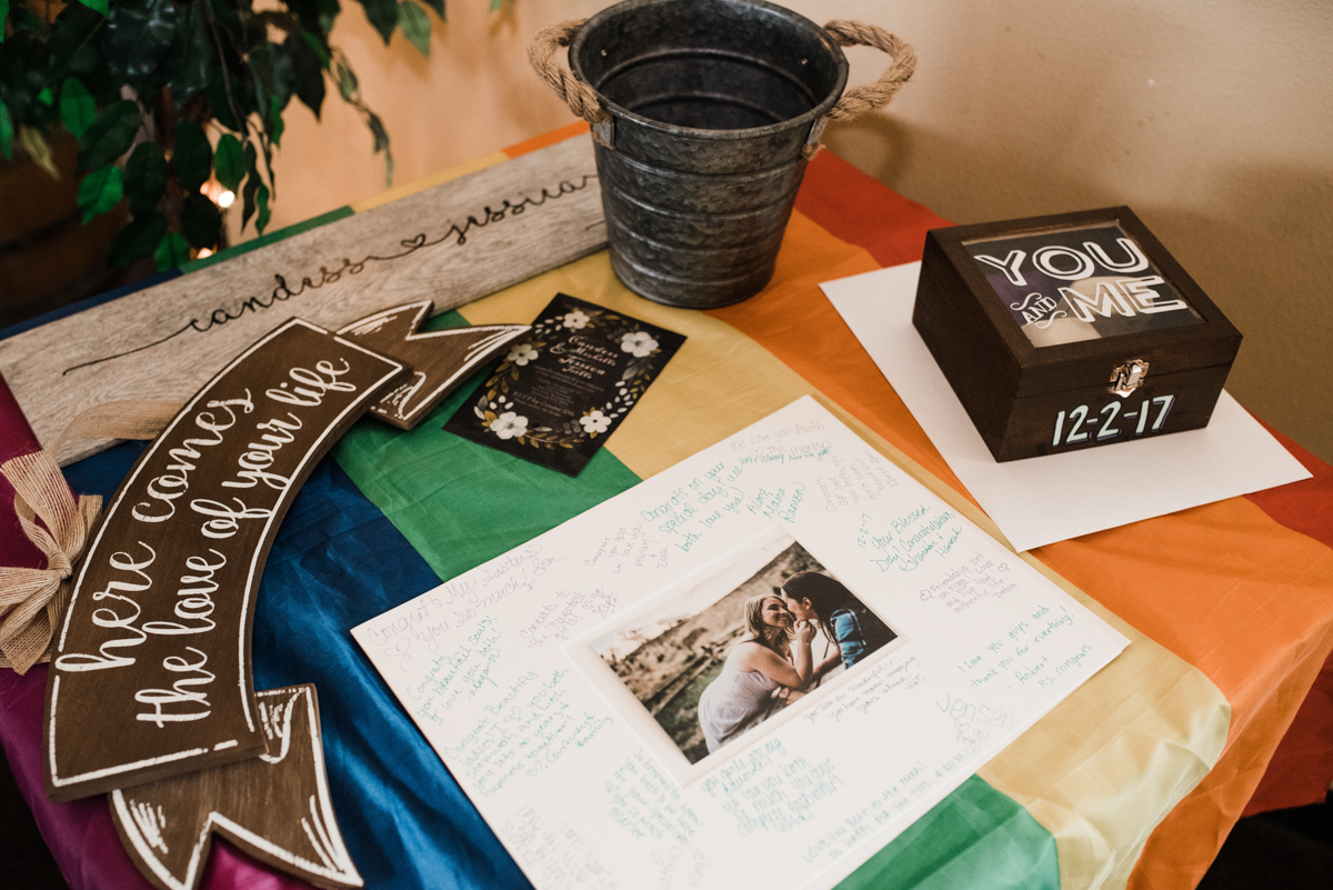 Rustic italian wedding table draped with LGBTQ+ flag; card box, picture, bucket, signs