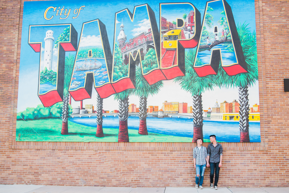 DOWNTOWN TAMPA ENGAGEMENT MICHAEL AND NICHOLAS IN FRONT OF TAMPA MURAL