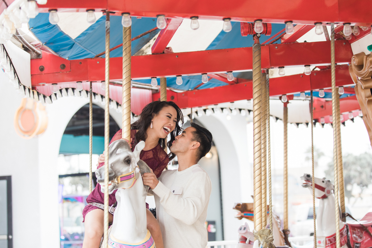belmont park engagement session san diego angela laughing on carousel horse with jamie standing beside her