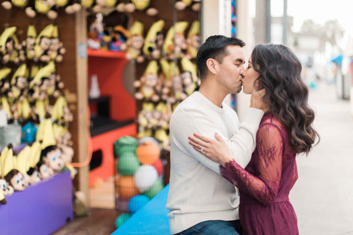 belmont park engagement session san diego kiss at game booth