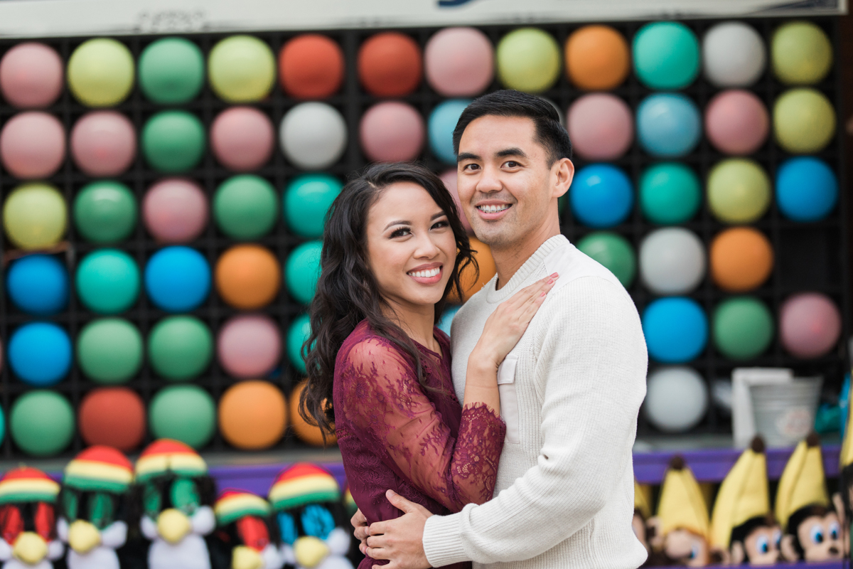 belmont park engagement session san diego embrace in front of darts game