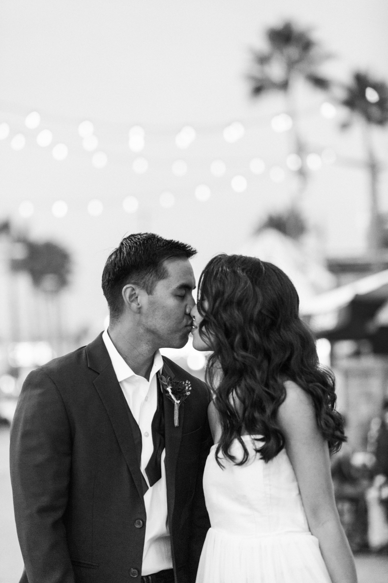 belmont park engagement session san diego kiss under park string lights