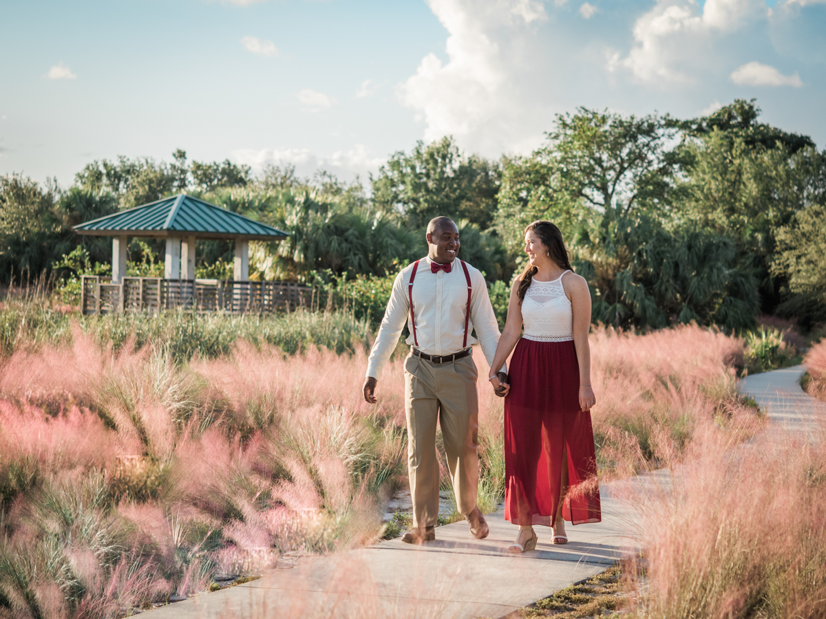 BOCA RATON ENGAGEMENT SESSION KELSEY AND KRIS WALKING DOW GARDEN PATH HOLDING HANDS