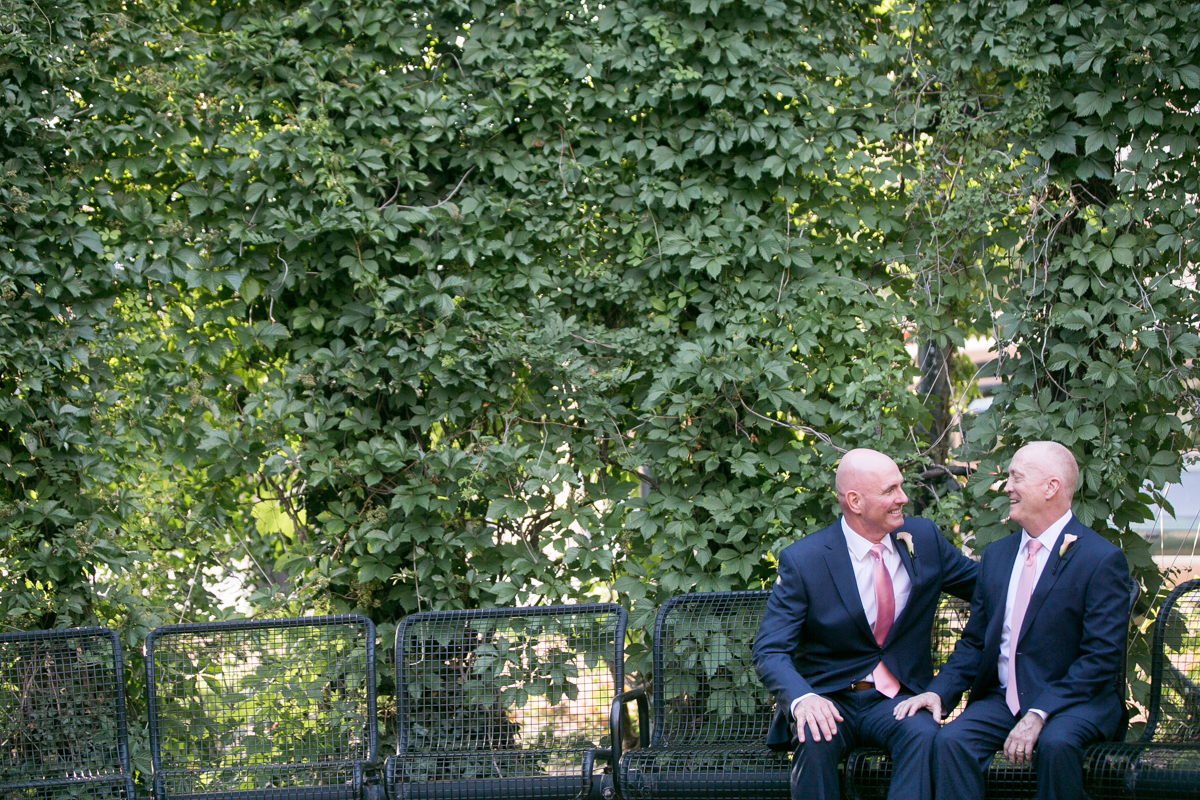 elegant, heartfelt alexandria, va wedding candid of grooms on terrace in front of tree wall