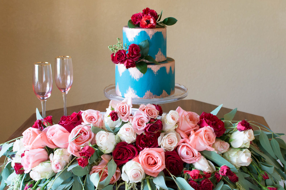 B ohemian Styled Shoot table with cake, champagne glasses, and rose arrangement
