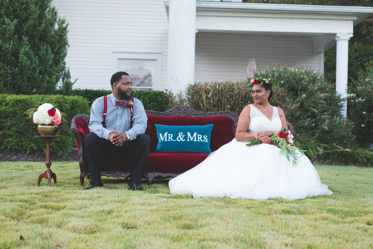 """B ohemian Styled Shoot couple on sofa outside with pillow reading """"mr. and mrs."""""""