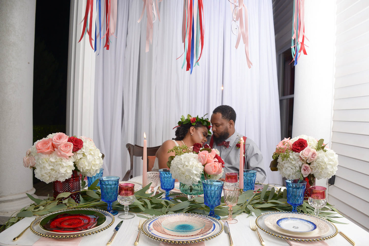 B ohemian Styled Shoot embrace at table under ribbon decorations