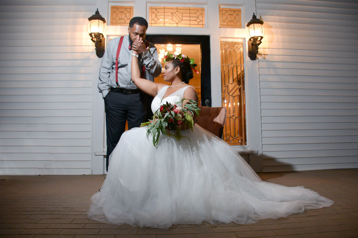 B ohemian Styled Shoot bride on chair and groom kissing her hand