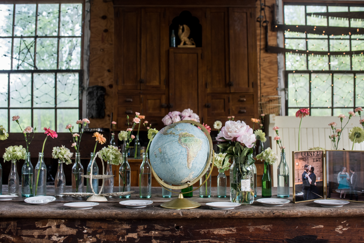 saratoga springs wedding table set with plates, flowers, and a globe