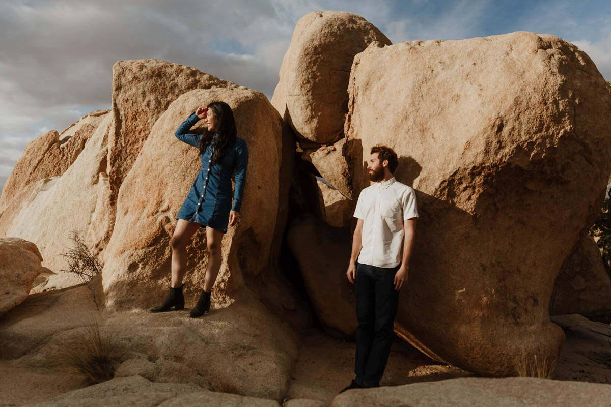 joshua tree california engagement session couple standing on rock cluster looking out at desert sunset