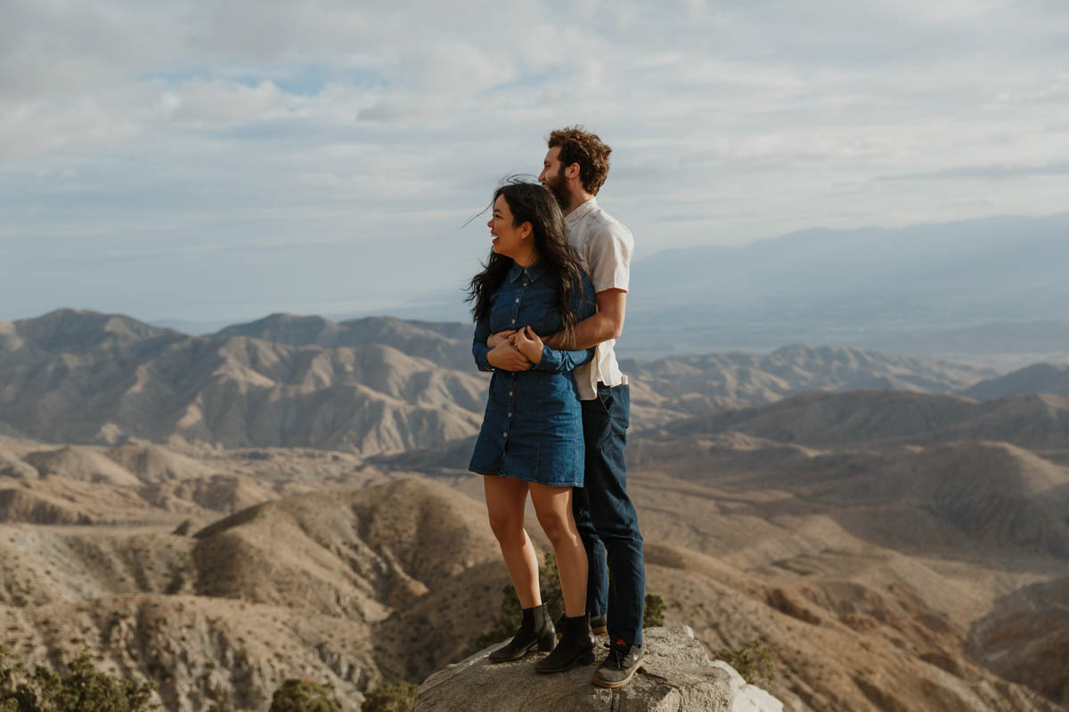 joshua tree california engagement session embrace on top of rock, mountains in background