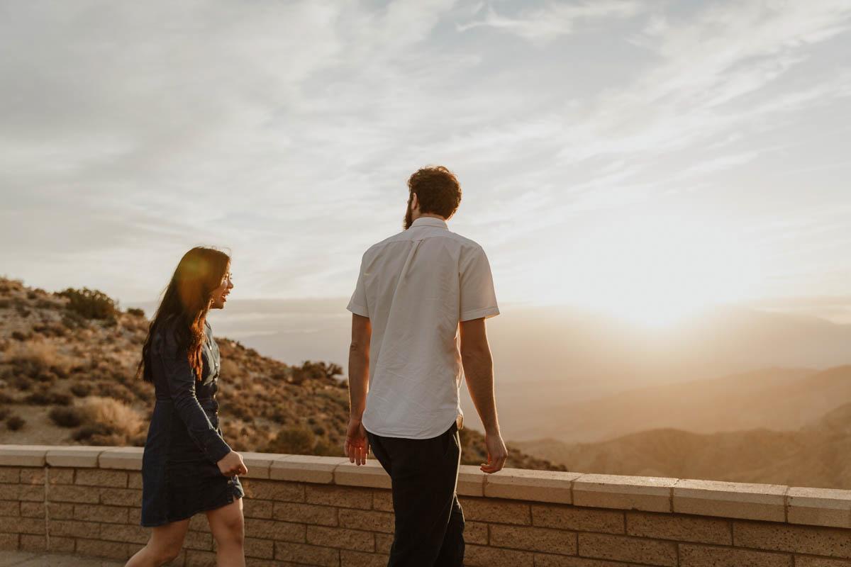 joshua tree california engagement session couple at brick wall facing sunset