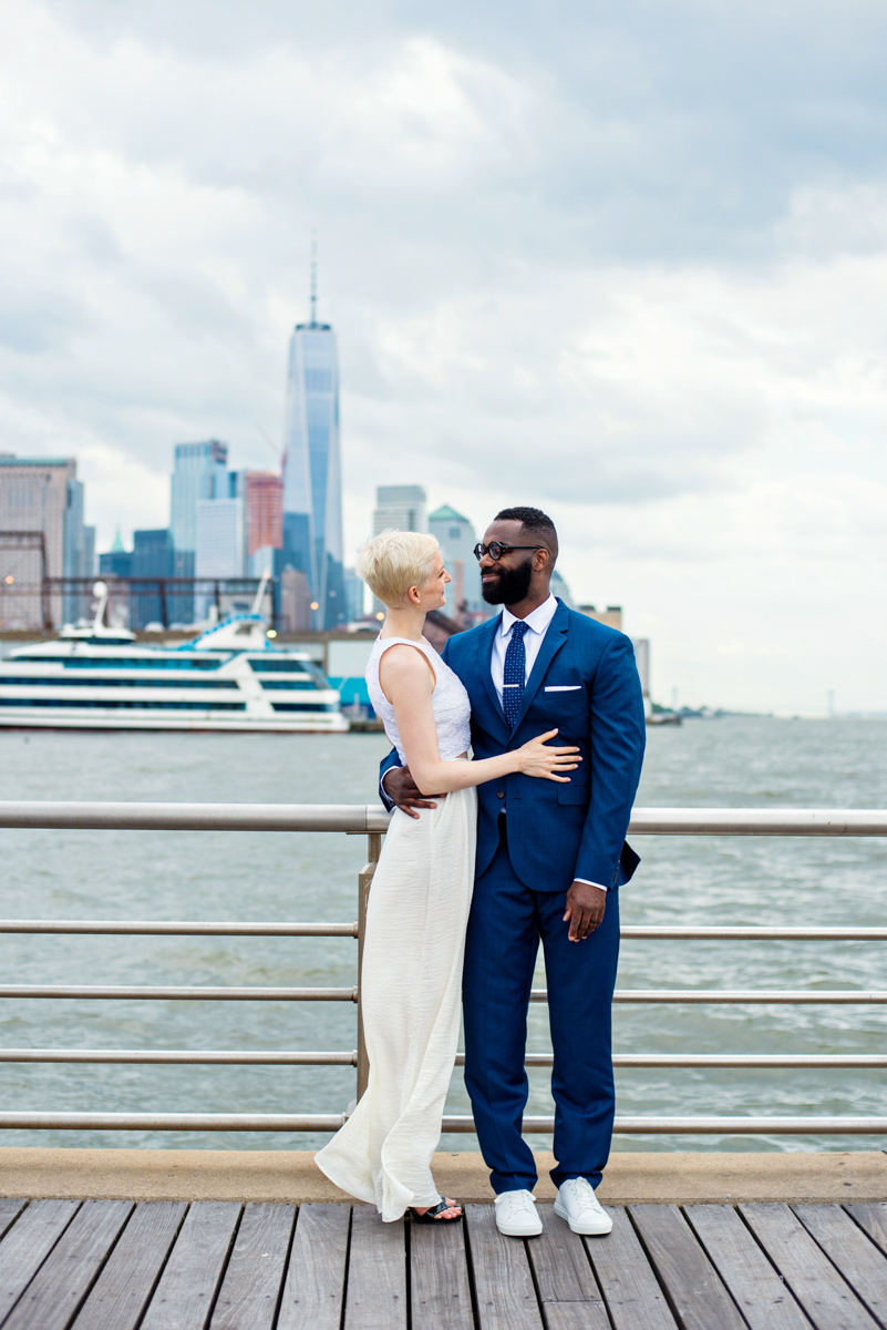 intimate new york elopement couple on pier with city skyline in background