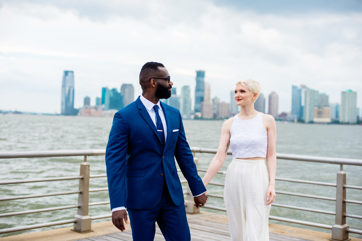 intimate new york elopement teddy and vanessa holding hands on pier, skyline in background