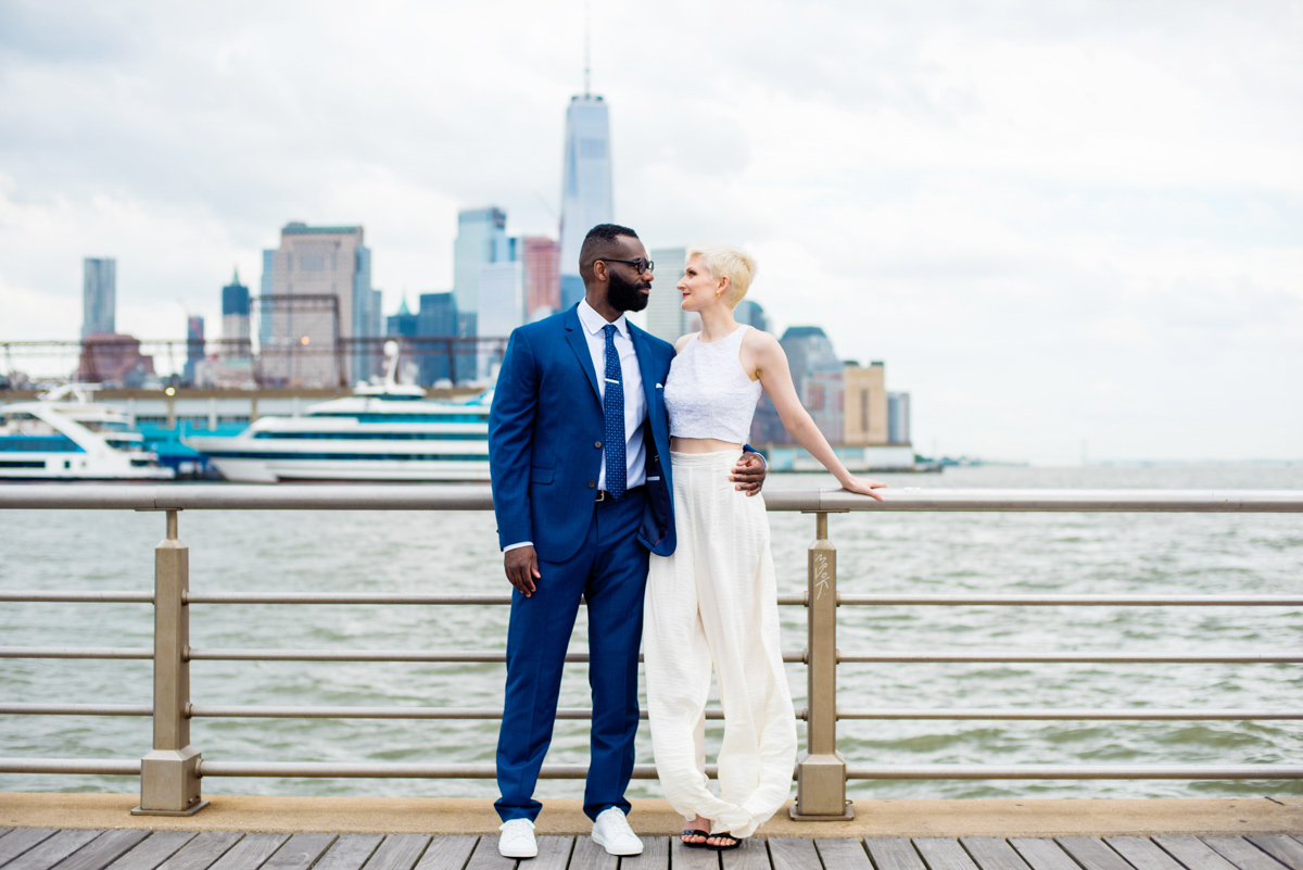 intimate new york elopement teddy with his arm around vanessa's waist at pier railing