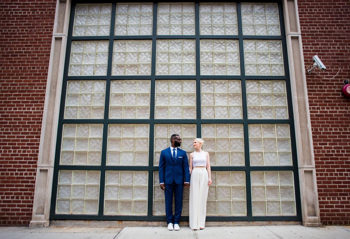 intimate new york elopement couple in front of brick wall set with opaque window grid