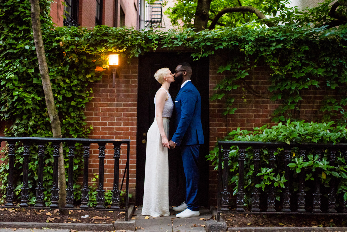 intimate new york elopement kiss in front of eave-covered brick wall