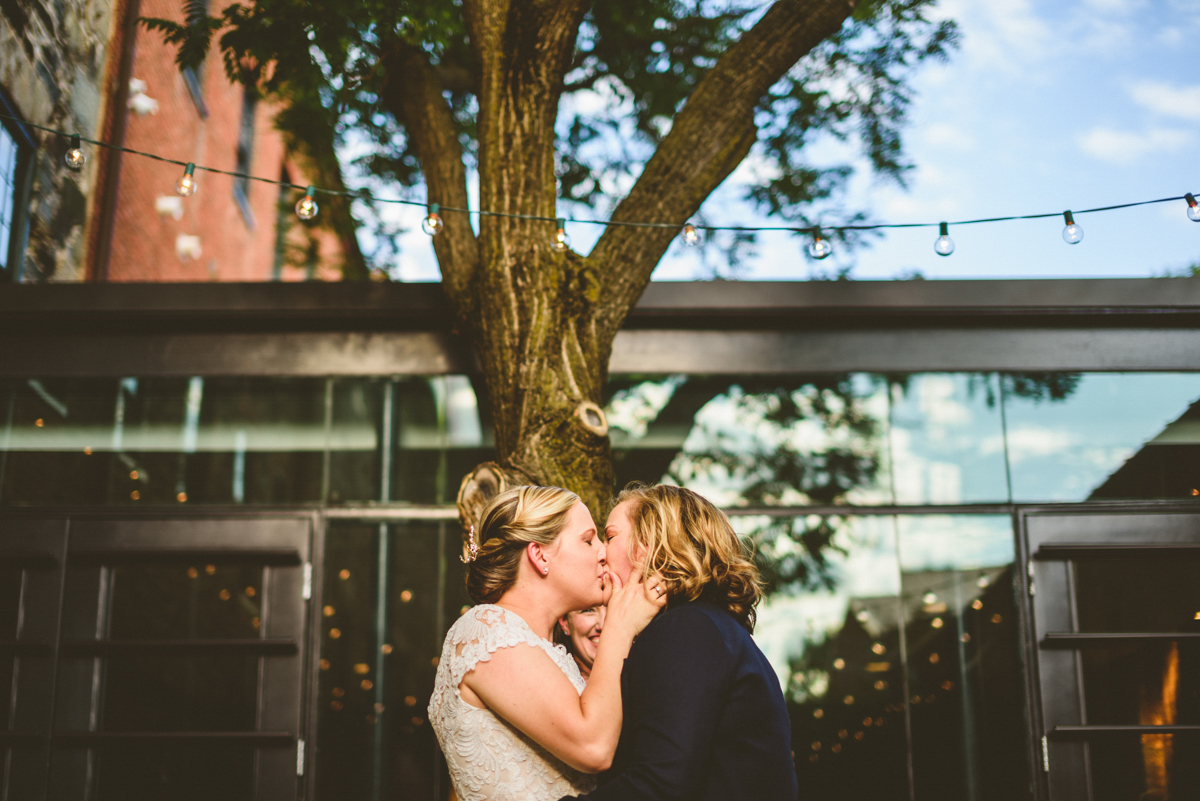 BALTIMORE WEDDING AT MOUNT WASHINGTON MILL DYE HOUSE KISS AT CEREMONY UNDER STRING LIGHTS