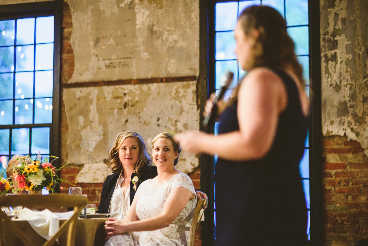 BALTIMORE WEDDING AT MOUNT WASHINGTON MILL DYE HOUSE GUEST GIVING SPEECH WHILE HOPE AND MEG LISTEN FROM TABLE
