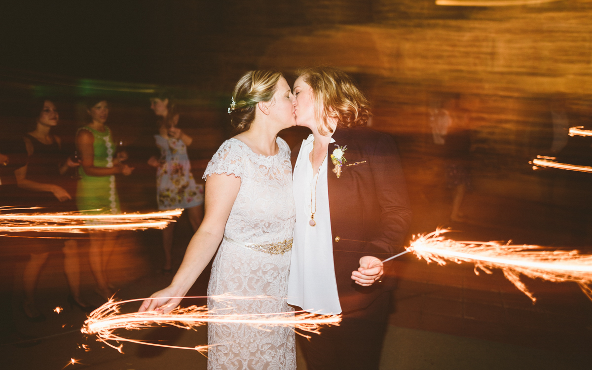 BALTIMORE WEDDING AT MOUNT WASHINGTON MILL DYE HOUSE COUPLE KISSES WHILE HOLDING SPARKLERS