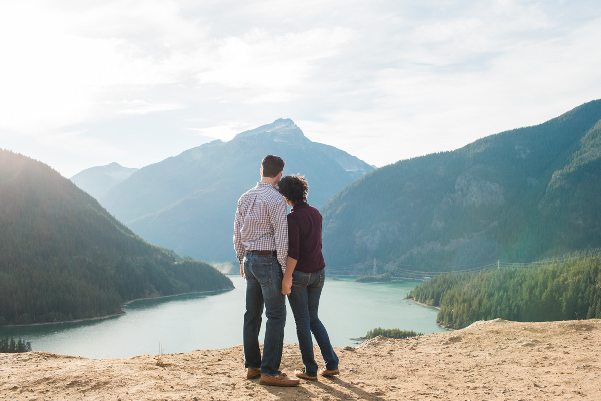 Diablo lake engagement session couple holding hands looking at mountains
