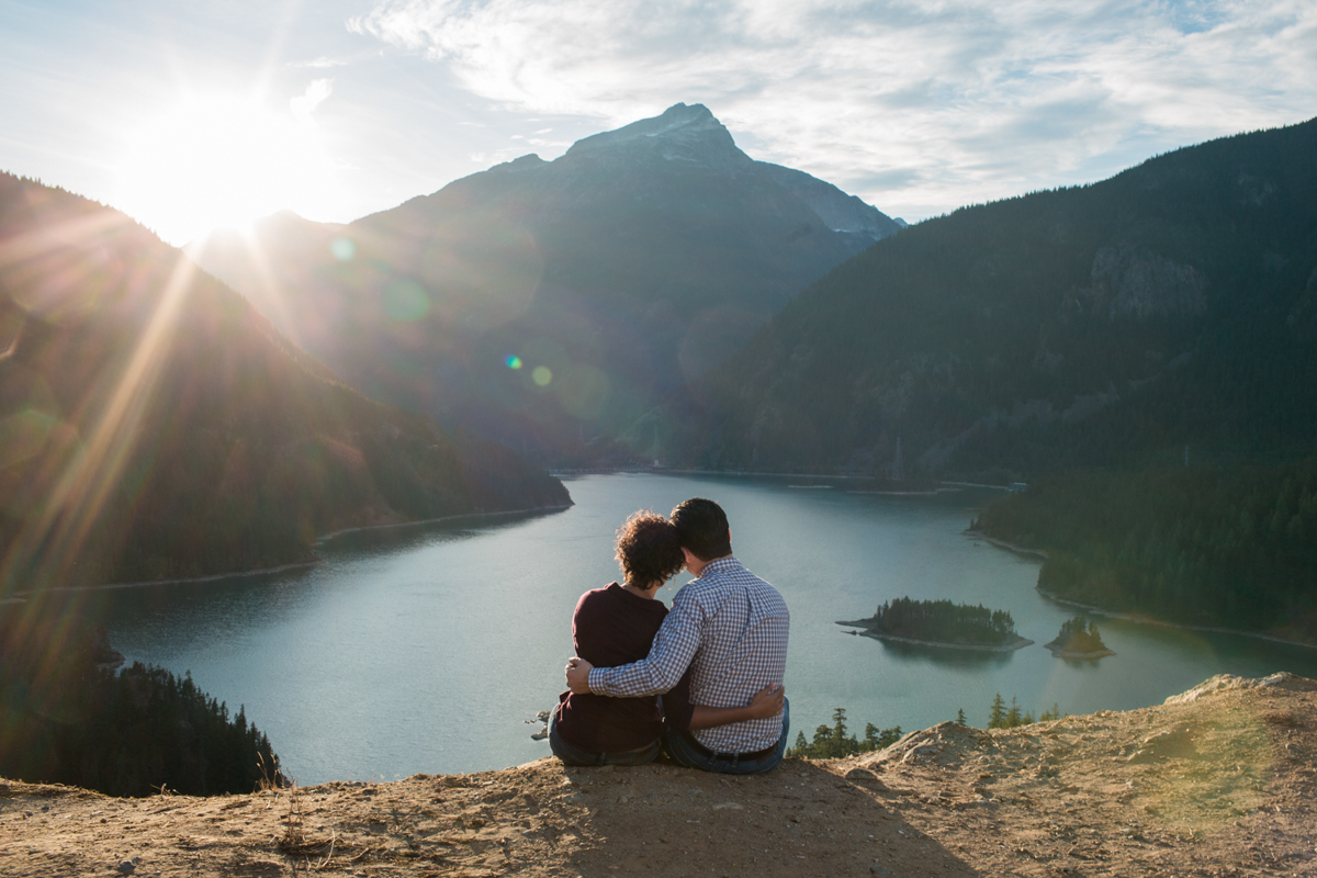 Diablo lake engagement session couple sitting on ledge looking at sun setting behind mountains