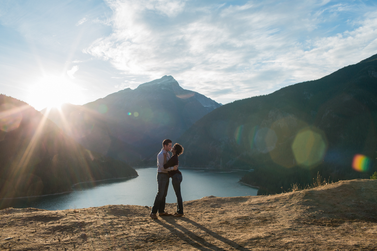 Diablo lake engagement session embrace overlooking mountain with sun setting
