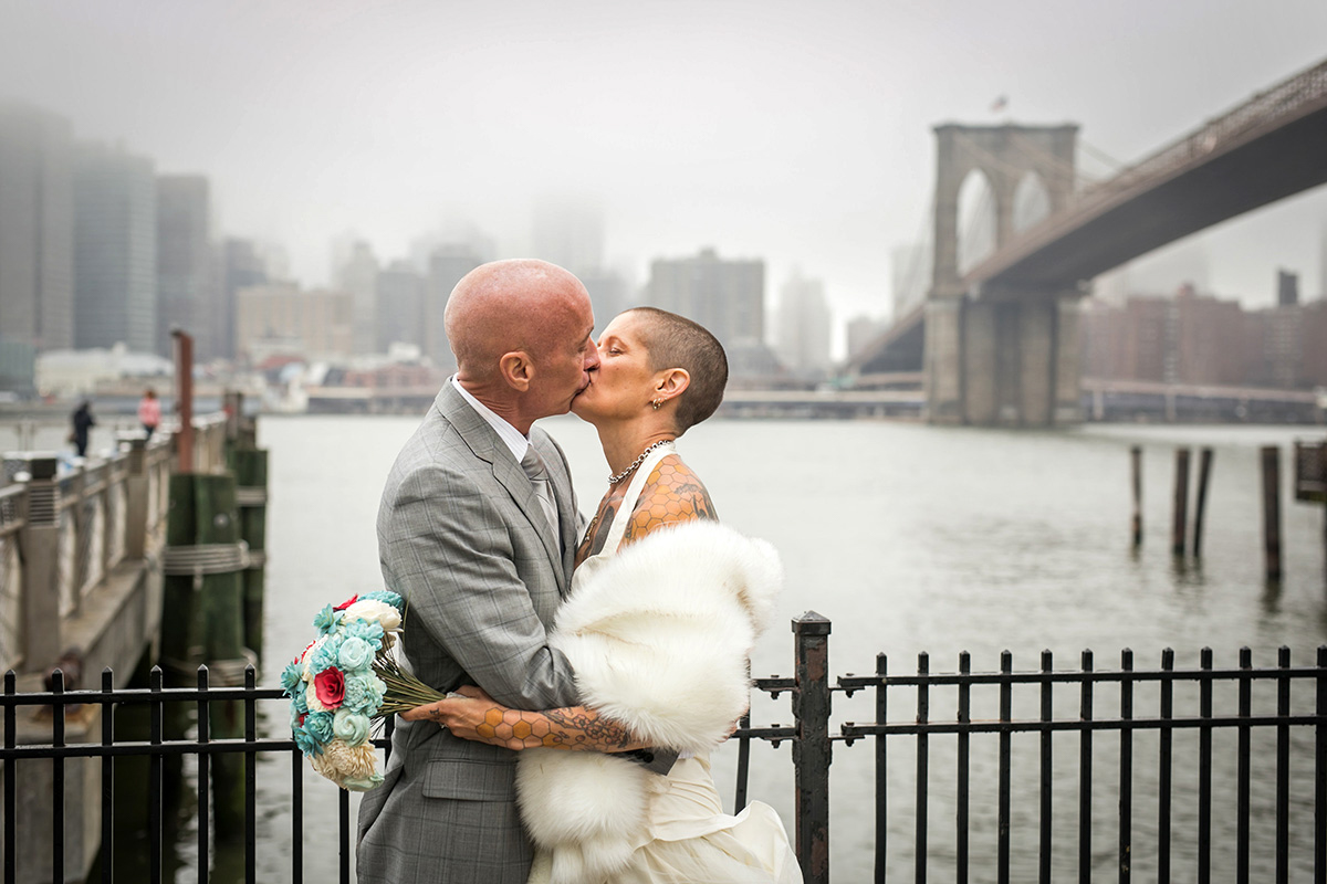 tattooed feminist elopement nyc kiss on boardwalk, river and bridge in background
