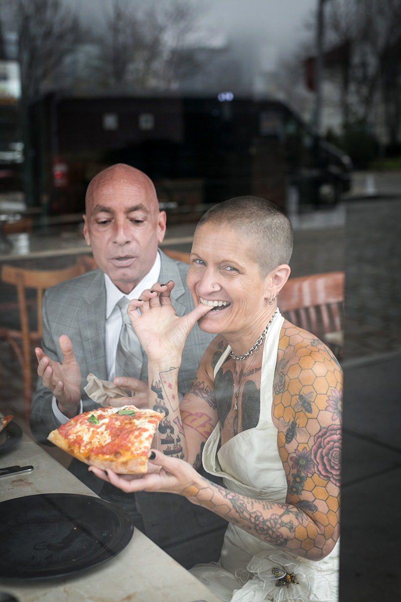 tattooed feminist elopement nyc couple having pizza, inger smiling for camera